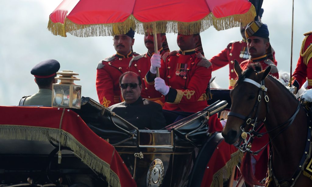 Pakistan's President Mamnoon Hussain rides a horse-drawn carriage escorted by presidential guards as he arrives at the venue for a Pakistan Day military parade in Islamabad